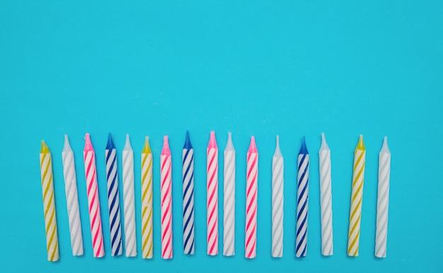 Kleurrijke kaarsen worden op een rij geplaatst voor een verjaardagstaart op een blauwe achtergrond