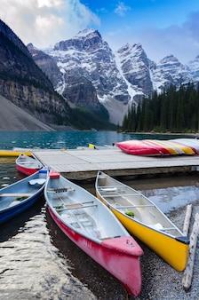 Kleurrijke kano's aangemeerd bij moraine lake in banff national park, canada