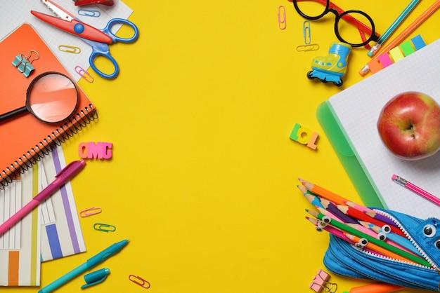 Kleurrijke kantoor- en studentenbenodigdheden op geel