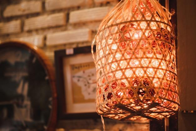 Kleurrijke katoenen bal gloeilampen die in de mand op de muur hangen met bokehachtergrond.