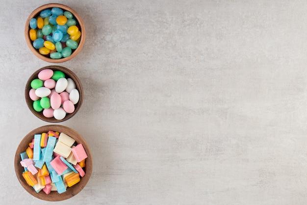 Kleurrijke kauwgom in kommen op een stenen tafel.