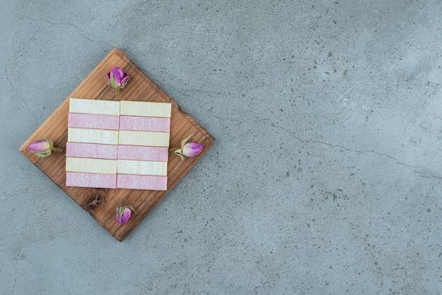 Kleurrijke kauwgom met gedroogde rozen op een houten bord.