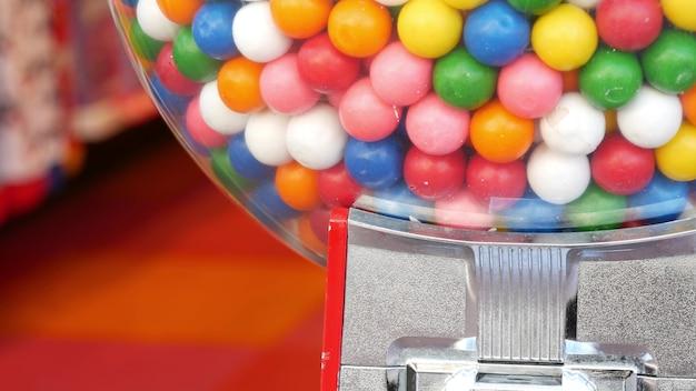 Kleurrijke kauwgomballen in automaat. veelkleurig tandvlees in dispenser. kauwgom snoepjes.