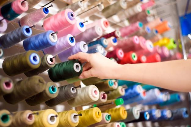 Kleurrijke kegels en spoelen van draad in een atelier. tailoring, kledingindustrie, designer workshop concept.