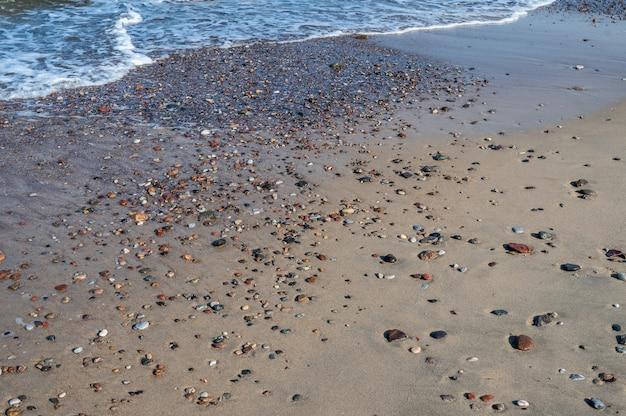 Kleurrijke keien op het zand bij de zee