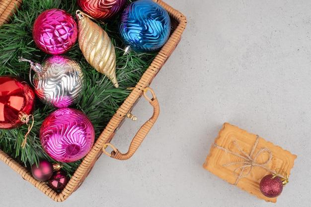 Kleurrijke kerstballen in mand met koekjes in touw.