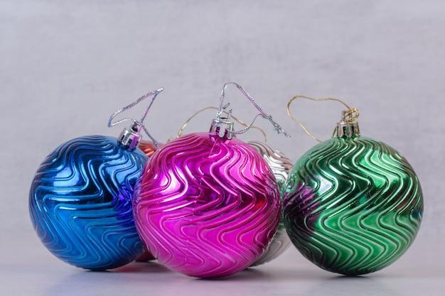 Kleurrijke kerstballen op witte tafel.
