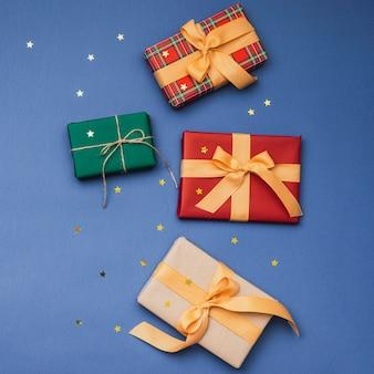 Kleurrijke kerstcadeaus met lint en gouden sterren
