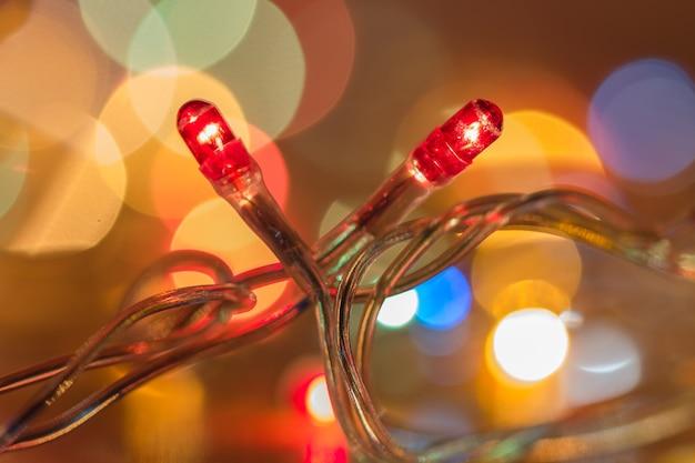 Kleurrijke kerstmislichten over een rode achtergrond
