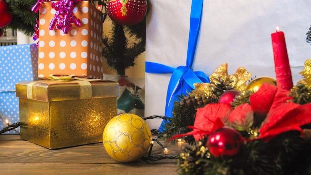 Kleurrijke kerstversieringen, geschenken en krans met kaarsen in de woonkamer