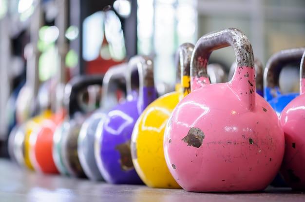 Kleurrijke kettlebells op een rij in een gymnastiek