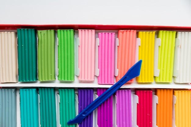 Kleurrijke kid's plasticine op wit oppervlak, kleurrijke deeg boetseerklei. veelkleurige briketten van zachte plasticine voor het modelleren met soft focus. kleurrijk plastic materiaal voor kunstonderwijs voor kinderen.