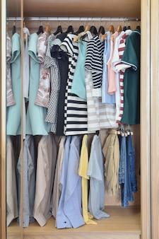Kleurrijke kleding die in garderobe hangt