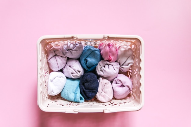 Kleurrijke kleding verticale opslag in huisgarderobe. kledingstukken in een doos op zachtroze achtergrond.