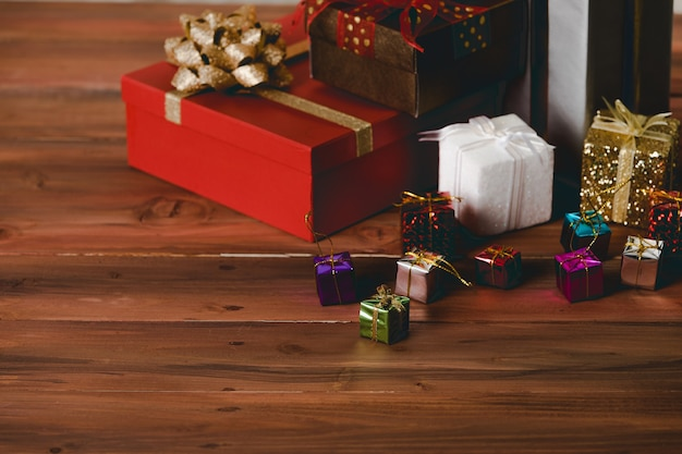 Kleurrijke kleine hangende decoratieve en grote handgeschept papier verpakte geschenkdozen met glanzende lintvlinderdas geplaatst op donkerbruine houten tafel op kerstavond verjaardagsfeestje of nieuwjaarsfestival.