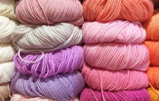 Kleurrijke kleuren wolgaren om te breien, ballen op de vitrine. roze, lila, beige kleuren.