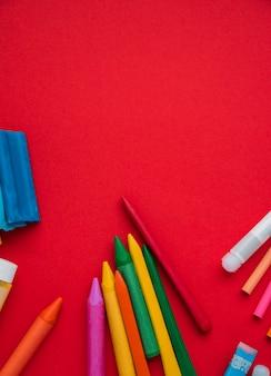 Kleurrijke kleurpotloden met klei en lijm over heldere rode achtergrond