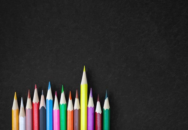 Kleurrijke kleurpotloodpotloden op zwart canvas met exemplaarruimte.