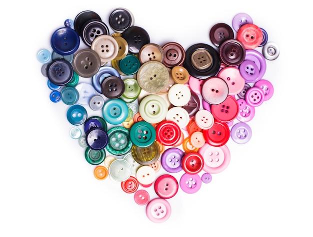 Kleurrijke knoppen als een hartvorm op wit wordt geïsoleerd