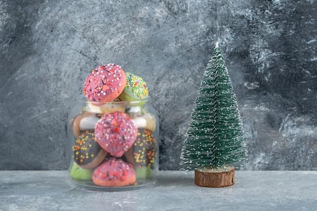 Kleurrijke koekjes met hagelslag in glazen pot en dennenboom.