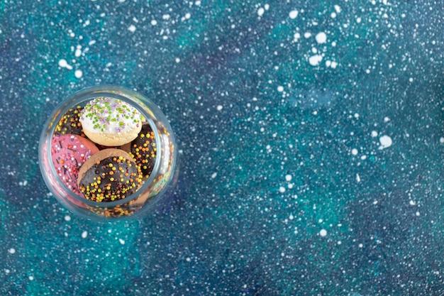 Kleurrijke koekjes met snoepjes in glazen pot.