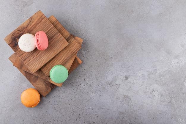 Kleurrijke koekjes op een houten bord op een grijze ondergrond