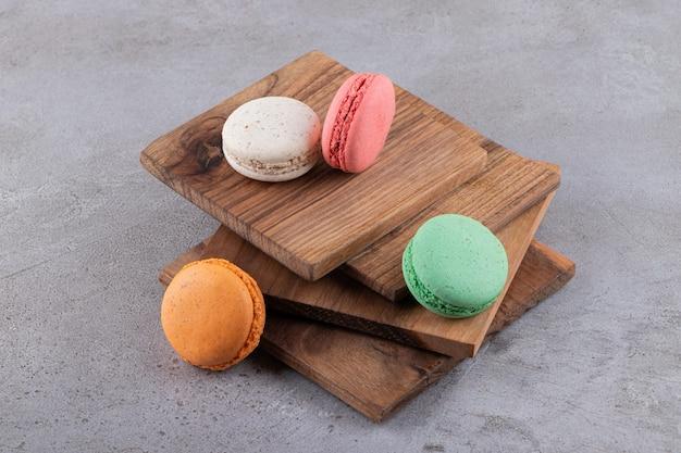 Kleurrijke koekjes op houten plankstapel over grijze achtergrond.