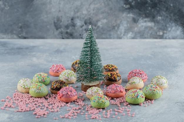 Kleurrijke koekjes versierd met hagelslag rond dennenboom.