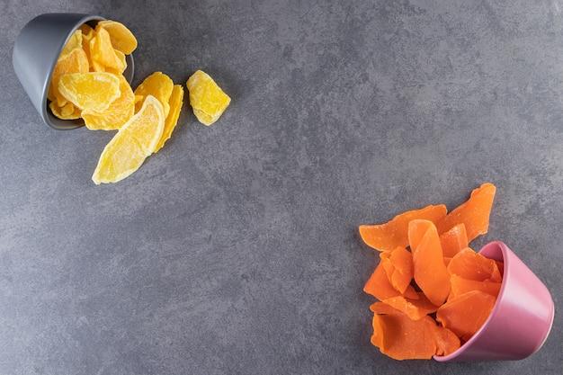 Kleurrijke kommen met gedroogde vruchtenpulp op stenen tafel.