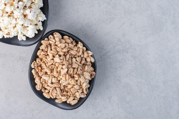 Kleurrijke kommen vol popcornsnoepjes en verspreide popcorn rond een met stof bekleed voetstuk op marmer.