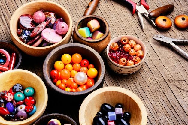 Kleurrijke kralen in houten kommen
