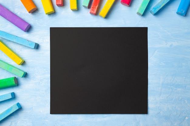 Kleurrijke krijtjes op blauwe achtergrond met kopie ruimte voor tekst. terug naar school-concept
