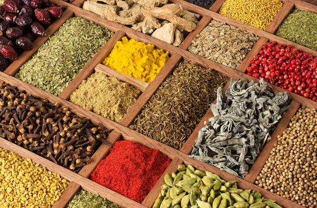 Kleurrijke kruiden en specerijen in houten bakjes.