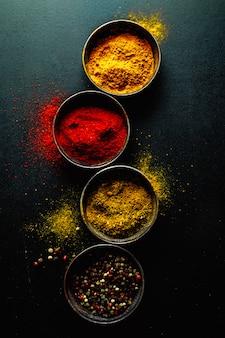 Kleurrijke kruiden op donkere tafel