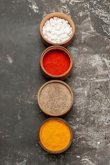 Kleurrijke kruiden vier kommen kleurrijke kruiden op de zwarte tafel