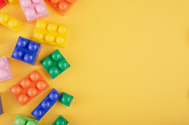 Kleurrijke kubussenblokken op gele achtergrond met exemplaarruimte voor tekst. plat leggen. bovenaanzicht.