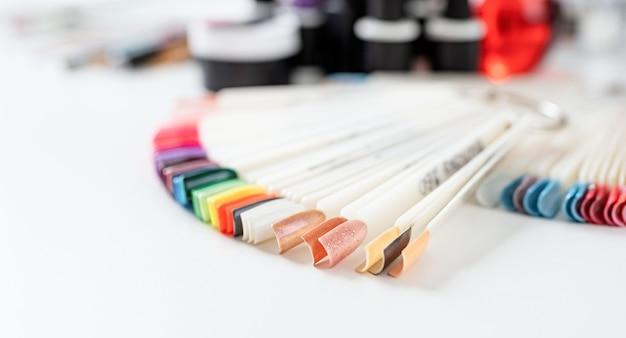 Kleurrijke kunststof nagel tips met verschillende nagel ontwerpen op tafel in manicuresalon