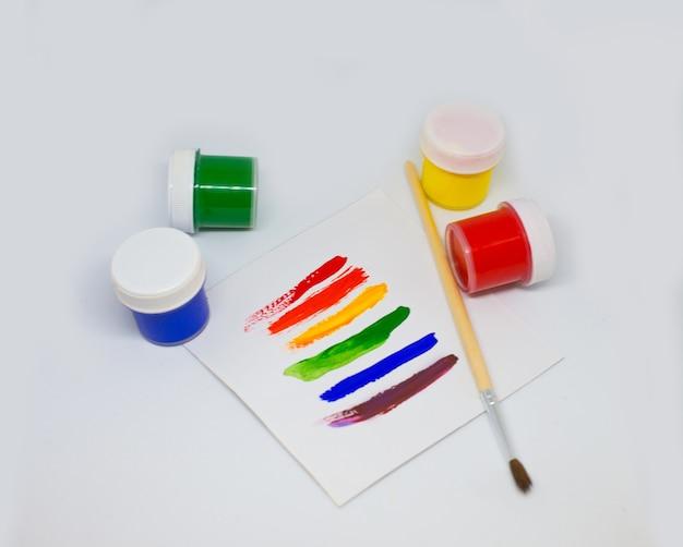 Kleurrijke lgbt-regenboogtekening op wit papier met acrylverf en penseel