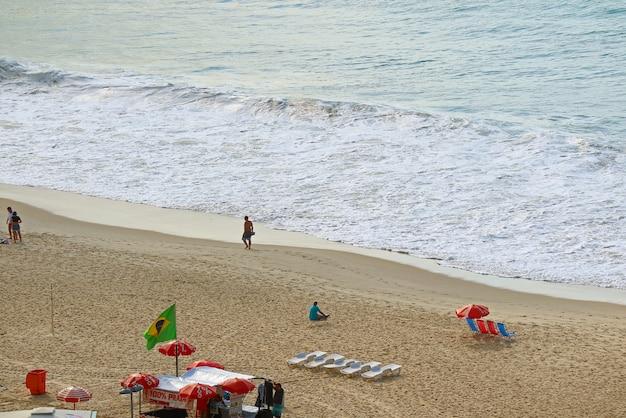 Kleurrijke ligstoelen en parasols op het golvende copacabana-strand, rio de janeiro, brazilië