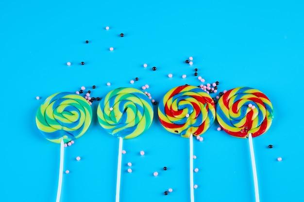 Kleurrijke lollies op blauwe achtergrond met sproeiers.