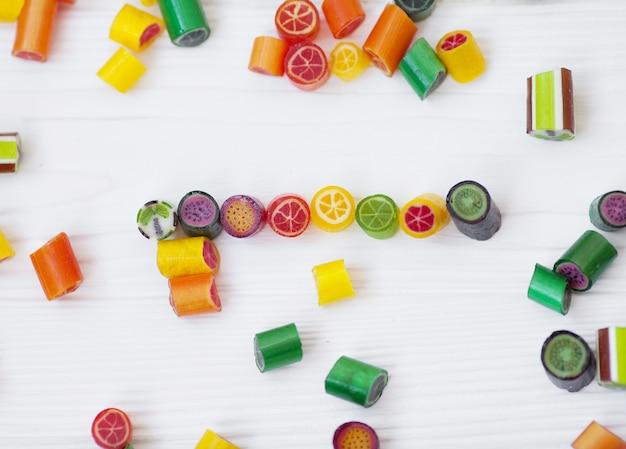 Kleurrijke lollies, snoep stokken en zoete snoepjes mix op houten achtergrond