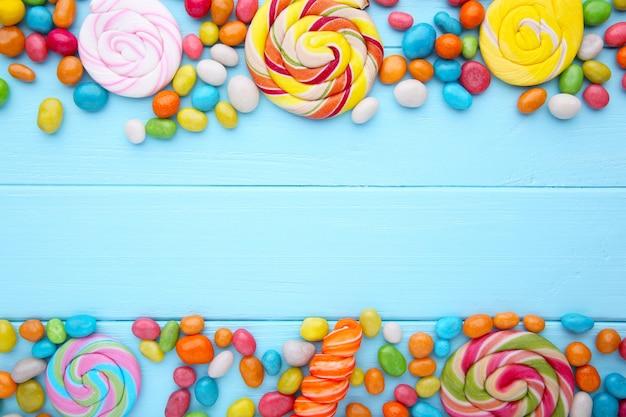 Kleurrijke lollys en verschillend gekleurd rond suikergoed op blauwe houten achtergrond