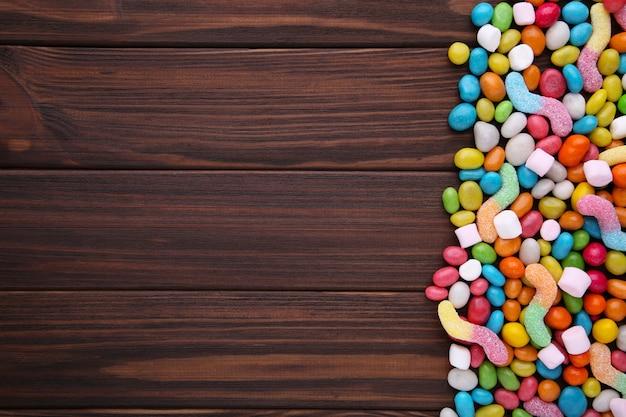 Kleurrijke lollys en verschillend gekleurd rond suikergoed op bruine houten achtergrond