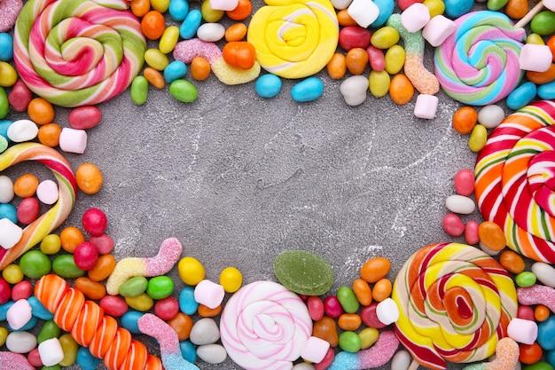 Kleurrijke lollys en verschillend gekleurd rond suikergoed op concrete achtergrond
