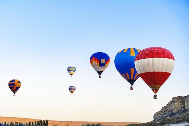 Kleurrijke lucht ballonnen vliegen in de heldere hemel in de buurt van enorme witte berg op zonnige dag