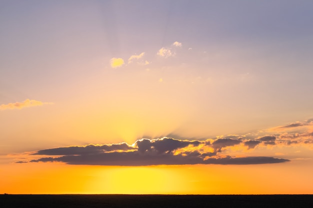 Kleurrijke lucht tijdens zonsondergang boven een smalle strook veld