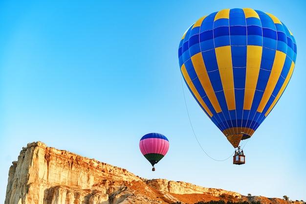 Kleurrijke luchtballons die in duidelijke hemel dichtbij reusachtige witte berg vliegen