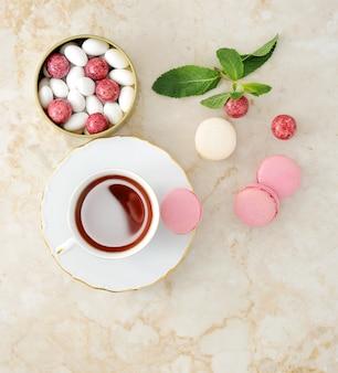 Kleurrijke macaron met een kopje thee