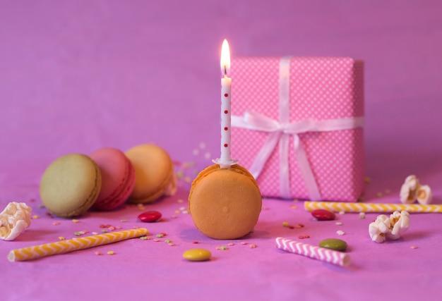 Kleurrijke macaron verjaardagstaart met brandende kaars