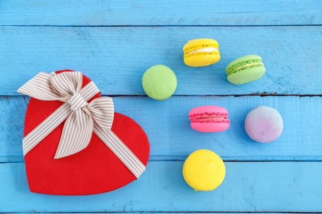 Kleurrijke macaronkoekjes en een hartvormig vak op een blauwe houten uitstekende lijst